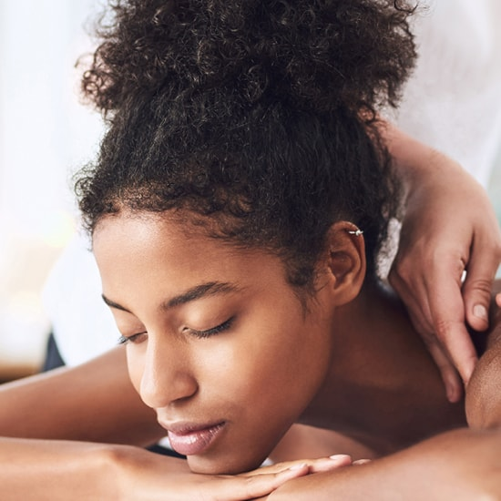 Lady enjoying a massage at the spa square image