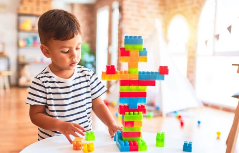 Kid playing with colourful blocks web banner