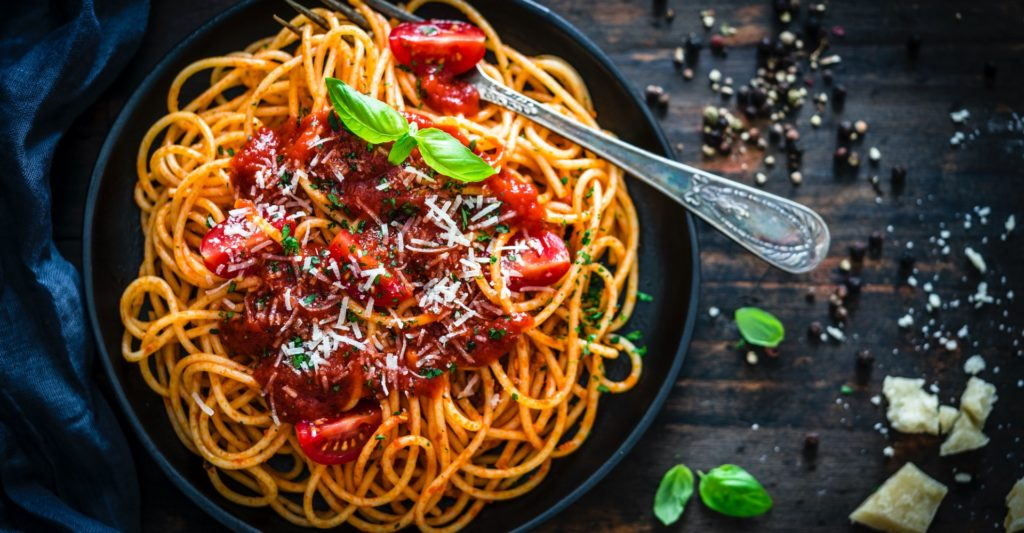 Spaghetti and tomatoes in a black bowl and silver fork lansscape image