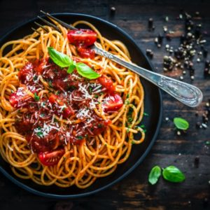 Spaghetti and tomatoes in a black bowl